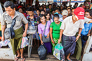"""17 JUNE 2013 - YANGON, MYANMAR: Passengers prepare to disembark from the Yangon-Dala Ferry in Dala. The ferry to Dala opposite Yangon on the Yangon River is the main form of transportation across the river. Every day the ferry moves tens of thousands of people across the river. Many working class Burmese live in Dala and work in Yangon. The ferry is also popular with tourists who want to experience the """"real"""" Myanmar. The rides takes about 15 minutes. Burmese pay about the equivalent of .06¢ US for a ticket.  Foreigners pay about the equivalent of about $4.50 US for the same ticket.    PHOTO BY JACK KURTZ"""