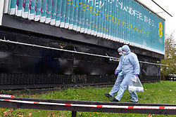 © Licensed to London News Pictures. 16/11/2012. Streatham, UK Forensic officers at the scene. The fire took place behind an advertising hoarding. Two people have died and another is in hospital with burns after a fire on wasteland in south London. Firefighters were called to the scene in Streatham High Road, Streatham, just after 02:20 GMT. Two bodies were found at the scene and a third person was taken to hospital for treatment. Crews took just over an hour to bring the fire under control. The incident is being investigated by the London Fire Brigade and the Metropolitan Police. Photo credit : Stephen Simpson/LNP