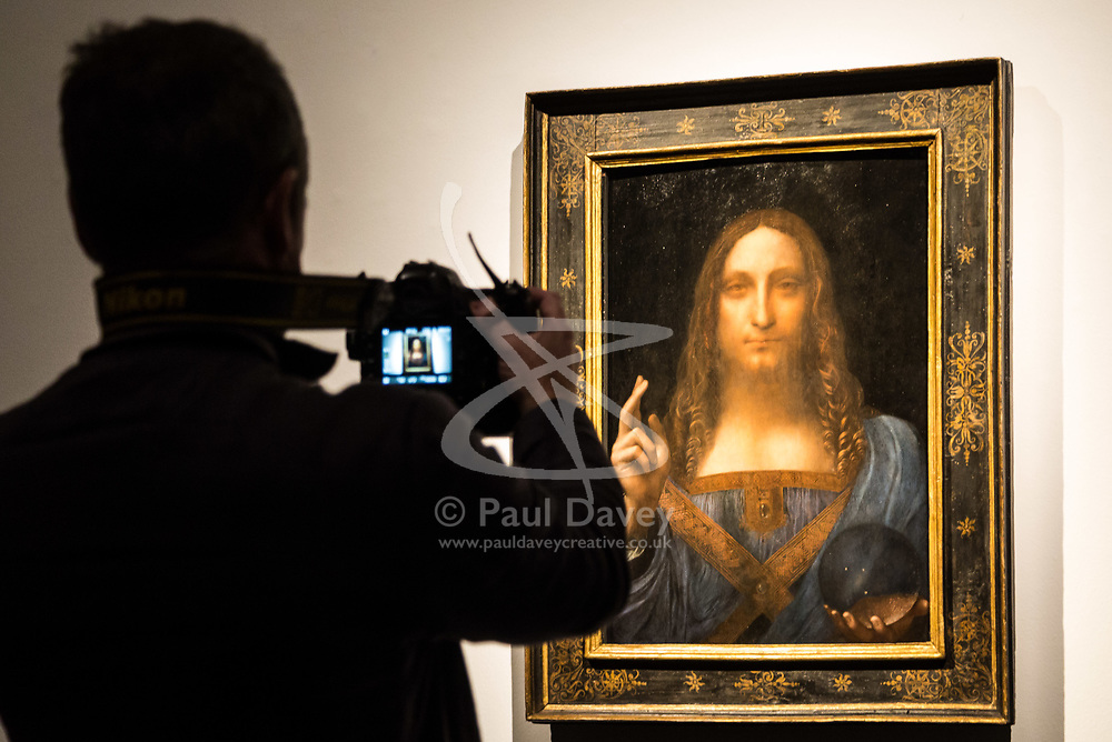 London, October 24 2017. A member of the press photographs Leonardo da Vinci's Salvator Mundi ('Saviour of the World') at a gallery preview at Christie's in London. The painting sold at Christie's in New York on 15 November 2017 for $450.3 million at Christie's New York, the highest price for any work of art. The painting is one of fewer than 20 known paintings by Leonardo, and the only one in private hands. © Paul Davey