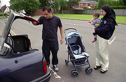 Mother holding young son while father finishes unloading pushchair from boot of car,