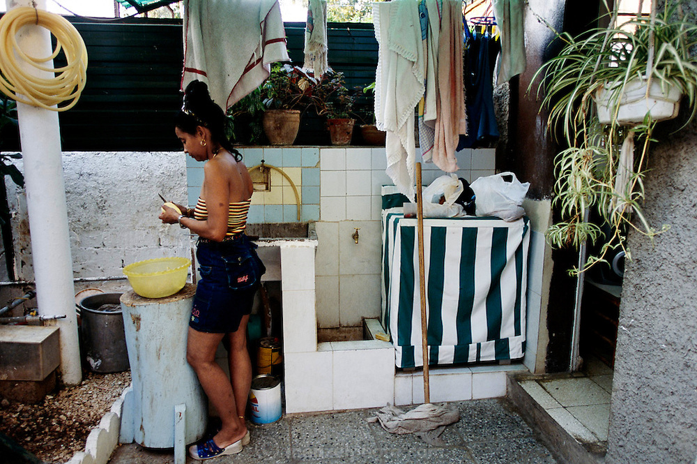 (MODEL RELEASED) Sandra Raymond Mundi peels vegetables for dinner in the outdoor courtyard kitchen area of their home in Havana, Cuba. (Supporting image from the project Hungry Planet: What the World Eats.)