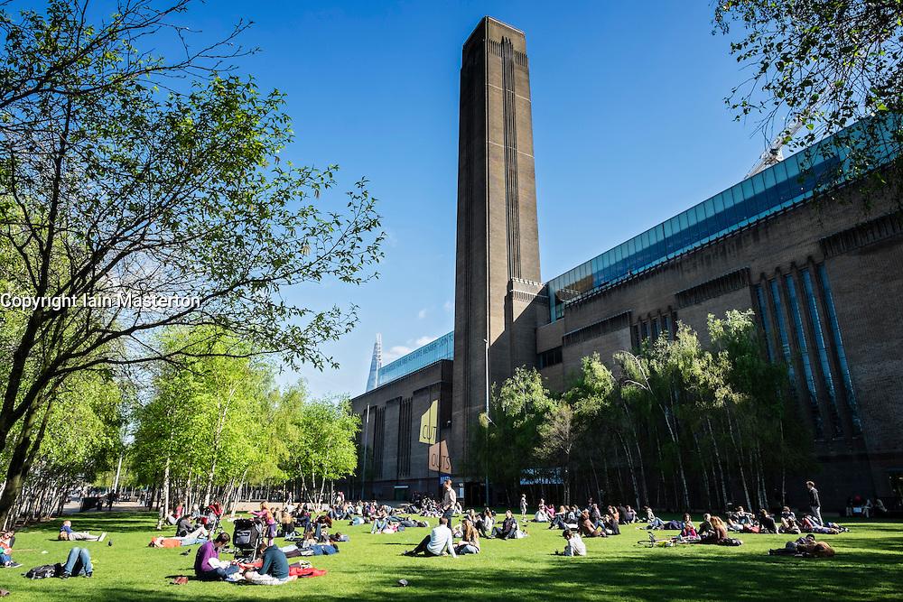 People relaxing on lawn outside Tate Modern art gallery in London United Kingdom