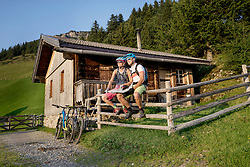 Couple of mountainbikers with map sitting on wooden fence, Zillertal, Tyrol, Austria