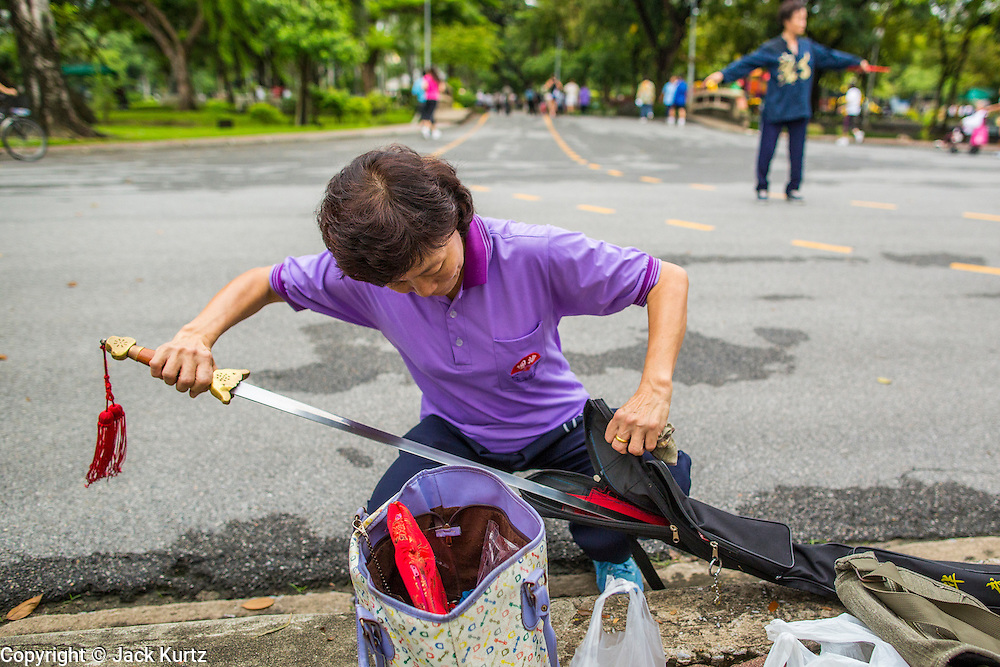 06 OCTOBER 2012 - BANGKOK, THAILAND:  A woman puts away her sword after doing Tai Chi exercises with it in Lumphini Park in Bangkok. The Thai government promotes exercise classes as a way staying healthy. Lumphini Park is 142 acre (57.6-hectare) park in Bangkok, Thailand. This park offers rare open public space, trees and playgrounds in the congested Thai capital. It contains an artificial lake where visitors can rent boats. Exercise classes and exercise clubs meet in the park for early morning workouts and paths around the park totalling approximately 1.55 miles (2.5km) in length are a popular area for joggers. Cycling is only permitted during the day between the times of 5am to 3pm. Smoking is banned throughout smoking ban the park. The park was created in the 1920's and named after Lumbini, the birthplace of the Buddha in Nepal.   PHOTO BY JACK KURTZ