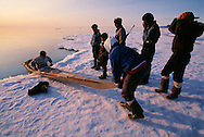 Greenland Inuit man teaches Canadian Inuit kids how to build and paddle kayaks, Pond Inlet, Baffin Island, Nunavut, Canada. Arctic