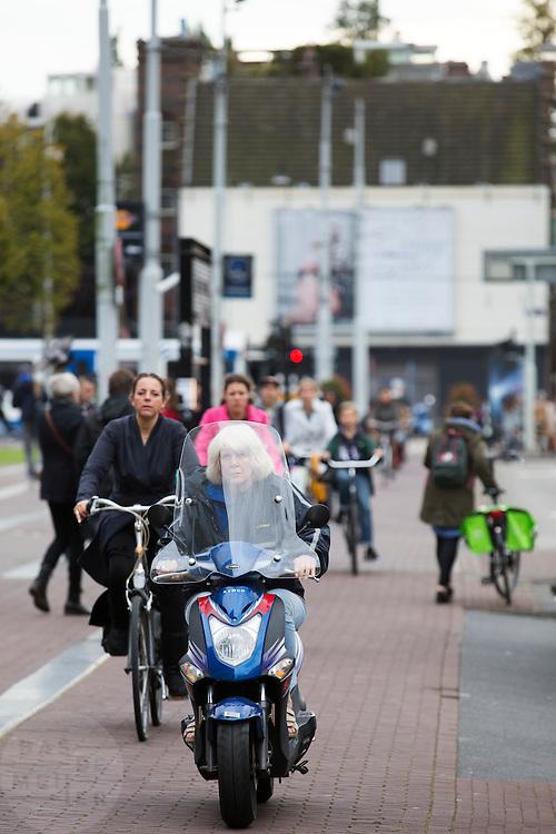 In Amsterdam rijden scooters tussen de fietsers over fietspad. De Fietsersbond wil samen met de gemeente Amsterdam dat bromscooters niet meer op het fietspad mogen rijden. De scooters veroorzaken veel overlast op de toch al volle fietspaden in de hoofdstad. Volgens onderzoek is het veiliger om de scooters op de hoofdrijbaan te laten rijden. Bovendien is het voor fietsers ongezond als de bromscooters met hun uitlaatgassen op het fietspad rijden. <br /> <br /> In Amsterdam scooters ride between the cyclists on the bike lane. The Dutch Cyclists Union and the municipality of Amsterdam want that moped scooters no longer allowed to ride on the bike lane.  The scooters are a nuisance to the already full bicycle lanes in the capital. According to research, it is safer to drive scooters on the main carriageway. Moreover, it is unhealthy for cyclists that moped scooters with their pollutions ride on the bike path.