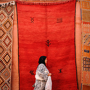 Moroccan woman in traditional dress and Islamic headscarf walking past hanging carpets in Marrakech, Morocco.