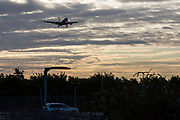An American Airlines Boeing 777 arrives across a car park at sunrise for landing at Heathrow airports north runway.  Heathrow Airport, London.