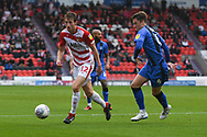 Tom Anderson of Doncaster Rovers (12) attacks forward with the ball under the attention of Alex Lacey of Gillingham (4) during the EFL Sky Bet League 1 match between Doncaster Rovers and Gillingham at the Keepmoat Stadium, Doncaster, England on 20 October 2018.