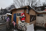 Roma squat in the snow, Christmas time with Santa Klaus , in one of the largest Roma encampments 'bidounvilles' outside Paris. Winter, Sarcelles, Paris suburbs, France<br /><br />Eastern european Roma migrants, often from Romania and Bulgaria, searching for better opportunities, they move near to western european cities. They typically are poor and live in squats, here around the periphery of Paris, in the suburbs 'banlieu' where they typically build ramshackle homes from recycled wooden panels and corrugated iron, or sometimes benders made from branches covered in tarpaulins. They live in woods and forest, industrial estates or derelict buildings. Life is especially difficult for them in the harsh conditions of winter and rain. Most of these camps get destroyed by police and Roma are eventually evicted, some deported back home or moving on to build another home. They often survive by recycling metal and electronic goods, selling recycled clothes and objects they find in trash bins, or through begging or playing music on the city streets or inside metro stations. Paris, France