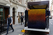 Art removal specialist workmen offload an artwork from the back of their van in Maddox Street, on 30th April 2019, in London, England.