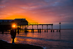 © Licensed to London News Pictures. 03/01/2018. Aberystwyth, UK. 03/01/2019. At the end of a grey dull and cold January day the sun makes a brief appearance as it sets over the Royal Pier in tandem with the roosting starlings  in Aberystwyth on the Cardigan Bay coast of west Wales. Photo credit: Keith Morris/LNP