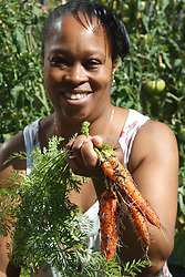 Woman with carrots in vegetable patch. Cleared for Mental Health issues.