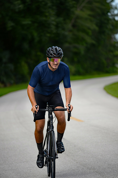 Cyclist riding hard on a road bike on curving road