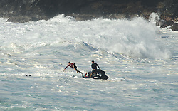 December 13, 2017 - Waimea Bay, HI, USA - WAIMEA BAY, HI - DECEMBER 13, 2017 - A lifeguard on a jetski brings a surfer to his lost surfboard after wiping out on a large wave at Waimea Bay. The big wave surfing spot only breaks in the winter when storms send large north swells toward the North Shore of Oahu. (Credit Image: © Erich Schlegel via ZUMA Wire)