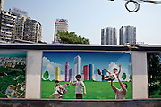 A poster on a wall next to a construction site shows happy Chinese families in Chongqing.