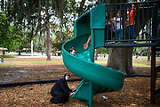 Jamila Alrazouk waits for granddaughter Jamila, 2, to reach her as uncle Momen Alsaloum sends her down a slide at the children's play area of a park in Tampa, Florida, U.S.