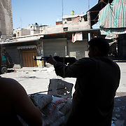 August 14, 2012 - Aleppo, Syria: A Free Syria Army (FSA) fighter shoots at government snipper's position in Babal Nassar neighborhood in Aleppo's old city. The Syrian Army have in the past ten days increased their attacks on residential neighborhoods where Free Syria Army rebel fights have their positions in Syria's commercial capital, Aleppo. (Paulo Nunes dos Santos/Polaris)