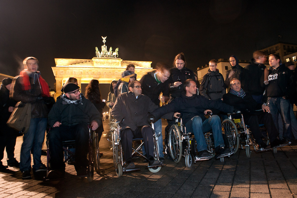 Siebter Tag des Hungerstreik der Flüchtlinge am Brandenburger Tor, Berlin Deutschland..Weil Polizeibeamte die Nutzung von Rollstuehlen bei der Kundgebung untersagen, setzten sich die Abgeordneten Oliver Höfinghoff (Piratenpartei)(1.v.l.), Özacn Mutlu (Grüne) (2.v.l.) und Hakan Tas (Die Linke) (1.v.r.) und der Anmelder der Mahnwache Dirk Stegemann (2.v.r.) aus Protest in Rollstuehle. Polizeibeamte schieben sie zur Seite, heben sie auf eine Bank und Beschlagnahmen die Rollstühle.