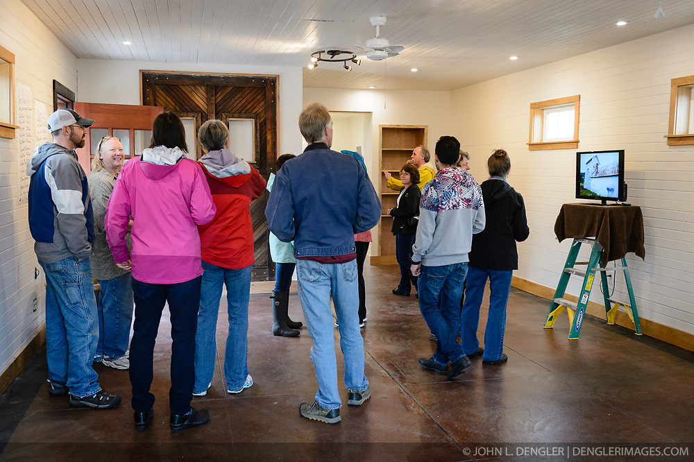 """Joanne Waterman (second from left) greets visitors to a recent open house celebrating the completion of the restoration of the fire hall on the grounds of historic Fort William H. Seward in Haines, Alaska.<br /> <br /> The fire hall was restored over a two-year period by owners Waterman and Phyllis Sage who also own the fort's original guardhouse, now a bed and breakfast, located next door to the fire hall.<br /> <br /> After being absent from the historic Fort Seward skyline since approximately the 1930s, the 60-foot tower of the fort's fire hall has been restored to its original height. The building and tower, built around 1904 in Haines, Alaska, was shortened to approximately half its height in the 1930s for unknown reasons. The restoration included rebuilding a missing 35-foot section of the 60-foot tower whose purpose was to dry fire hoses. The tower restoration was completed by building its four sections on the ground and then hoisting those sections with a crane into place on top of each other.<br /> <br /> Through the years, the historic Fort Seward area, a former U.S. Army post, has been referred to as Fort William H. Seward, Chilkoot Barracks, and Port Chilkoot. The National Historic Landmarks listing record for the fort says that """"Fort Seward was the last of 11 military posts established in Alaska during the territory's gold rushes between 1897 and 1904. Founded for the purpose of preserving law and order among the gold seekers, the fort also provided a U.S. military presence in Alaska during boundary disputes with Canada. The only active military post in Alaska between 1925 and 1940, the fort was closed at the end of World War II."""" <br /> <br /> The bottom portion of the fire hall is being leased as commercial space. Due to fire code restrictions there is no public access to the upper portion of the tower."""