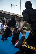 Jakarta, Indonesia - July 7, 2017: In the open space of a kampung in Jakarta, teenage boys and girls train in the Indonesian martial art called Baringin Sakti.