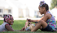 Zyiana Hudson, left, andMi'lana Beathea, both 6, play with dolls in the shade at their grandmother's house in South Bend on Tuesday.