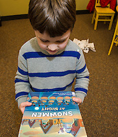 """Luke Dorval-Drown holds the book """"Snowmen At Night"""" read during Laconia Library's preschool story hour on Wednesday morning.  (Karen Bobotas/for the Laconia Daily Sun)"""