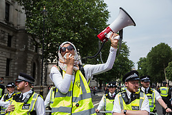 London, UK. 9th June, 2018. An organiser from Stand Up To Racism addresses anti-fascists protesting against the far-right March for Tommy Robinson in Parliament Street.