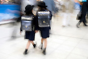 two little schoolchildren walking with large backpacks Tokyo Japan