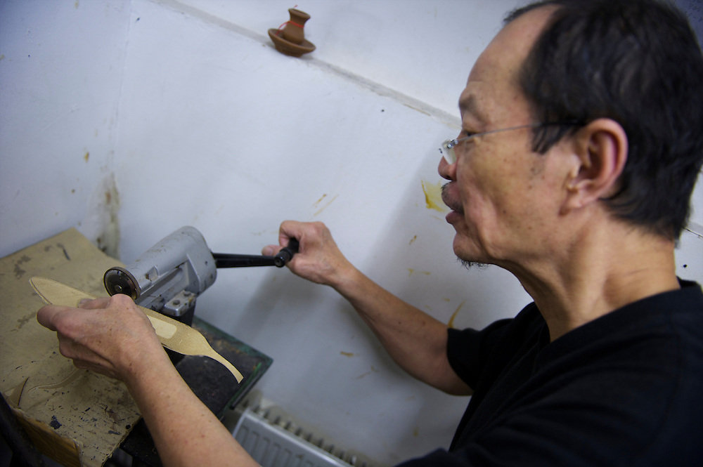 A shoemaker works on a pair of shoes in fashion designer Jimmy Choo's studio on Cannaught Street, London, March 22, 2010.