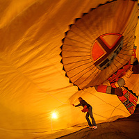 """120114  Adron Gardner/Independent<br /> <br /> Sheryl McClure helps straighten out an envelope of a hot air balloon during """"Holiday in New Mexico"""" festivities at the University of New Mexico in Gallup Monday."""