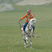 A young, costumed bareback rider approaches finish line of a 20km race at a traditional naadam festival on a remote pass near Muren in Hovsgol Aimag, Mongolia.