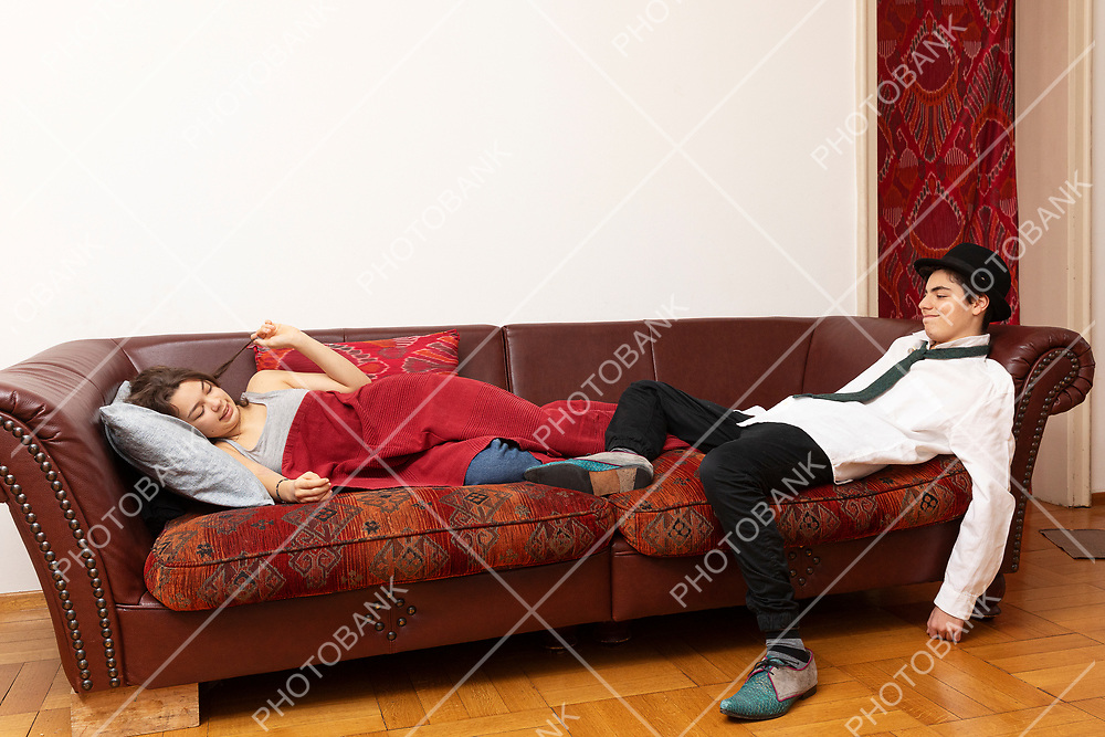 Young couple lying on the sofa. She is covered in a blanket. He is a businessman