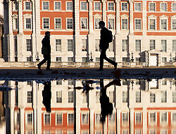 © Licensed to London News Pictures. 17/12/2018. London, UK. People making their way to work across Horse Guards Parade are reflected in a puddle and silhouetted against a sunlit Admiralty building. Photo credit: Peter Macdiarmid/LNP