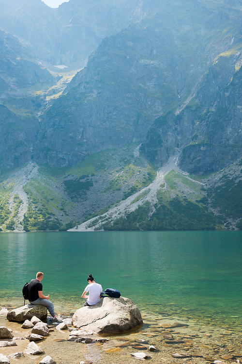 A man and woman sit beside the clear waters of Morskie Oko, a famous lake in southern Poland. Located within Tatra National Park, Morskie Oko sits at an elevation of about 1400 meters above sea level.