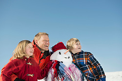 Family with snowman, smiling, Bavaria, Germany