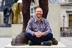© Licensed to London News Pictures. 31/05/2019. LONDON, UK.  Celebrated artist Thomas Houseago poses alongside his major installation of six recent sculptures in the courtyard of the Royal Academy of Arts in Piccadilly.  The installation forms part of The Summer Exhibition which rins 10 June to 12 August 2019.  Photo credit: Stephen Chung/LNP