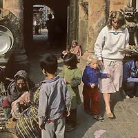 NEPAL, Kathmandu. Mother & young traveler (MR) shop in vegetable bazar.
