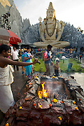A Hindu priest pours an offering of ghee onto a fire at the Shiva Temple, which is built into the Kid's Kemp Shopping Mall on Old Airport Road in Bangalore, India. (From the book What I Eat: Around the World in 80 Diets.) The 65-foot plaster statue of Lord Shiva sits in a lotus position before an amusement park-style Himalayan mountain-scape built of chicken wire and cement. This free popular attraction at the Kids Kemp shopping mall draws nearly 500,000 devotees on festival days.