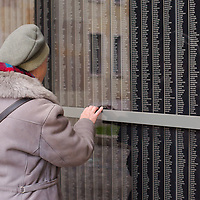 Woman stands in front of a wall bearing the names of victims at Budapest's Holocaust Memorial Centre, Hungary on January 27, 2013. ATTILA VOLGYI