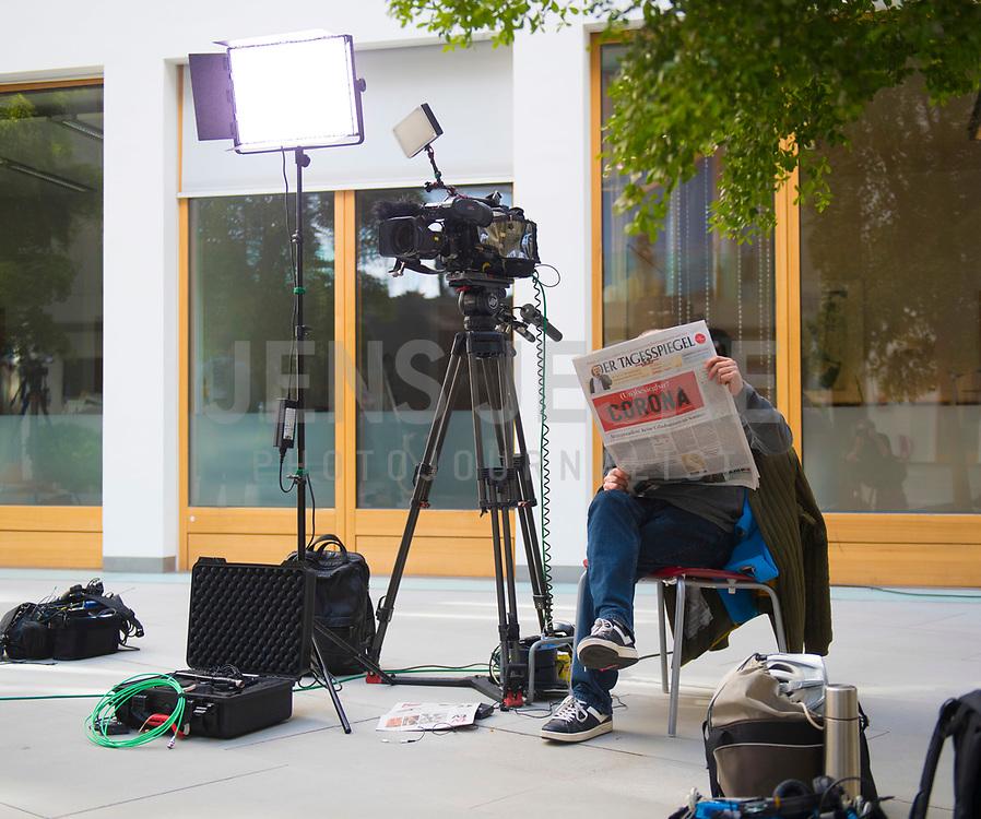 """DEU, Deutschland, Germany, Berlin, 09.04.2020: Ein Kollege vom Fernsehen liest in der Bundespressekonferenz den Tagesspiegel mit einer Titelseite zum Coronavirus (Covid-19): """"(Un)besiegbar? Corona"""""""