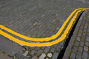 Freshly-Painted Double-Yellow Lines on a cobbled Street in Edinburgh, on 26th June 2019, in Edinburgh, Scotland.