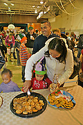 Hispanic mother helps child with cookies at multi racial Cape May holiday art and cookie event. Family activities Children, Foods,