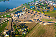 Nederland, Noord-Brabant, Werkendam, 28-10-2014; Ruimte voor de Rivier project Ontpoldering Noordwaard. Boven in beeld Fort Steurgat, omgeven door nieuwe dijk (primaire waterkering). De bandijk is reeds voorzien van een doorlaat annex brug, onder in beeld nieuwe terp voor (historische) boerderij.<br /> De Noordwaard wordt ontpolderd door de dijken aan de rivierzijde gedeeltelijk af te graven, hierdoor kan de Nieuwe Merwede bij hoogwater via de Noordwaard sneller naar zee stromen. Gevolg van de ingrepen is ook dat de waterstand verder stroomopwaarts zal dalen.<br /> National Project Ruimte voor de Rivier (Room for the River) By lowering and / or moving the dike of the Noordwaard polder the area will become subject to controlled inundation and function as a dedicated water detention district. Houses and farmhouses will be constructed on new dwelling mounds. <br /> luchtfoto (toeslag op standard tarieven);<br /> aerial photo (additional fee required);<br /> copyright foto/photo Siebe Swart