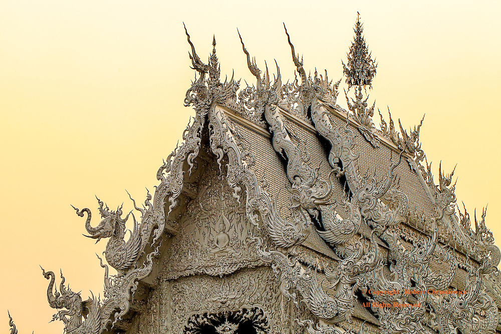 Ornate White Temple:  The intricately ornate roof of Wat Rong Khun (better known as the White Temple) is quite surrealistic under a yellow evening's sky, Chiang Rai Thailand.