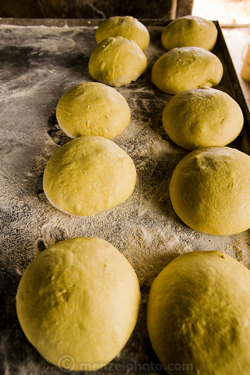 Fresh dough, about to be baked in circular ovens, in Akbar Zareh's bakery in the province of Yazd, Iran. (Akbar Zareh is featured in the book What I Eat: Around the World in 80 Diets.)  The son of a baker, Zareh began working full-time at age 10 and regrets that he didn't attend school and learn how to read and write. By working 10 hours a day, every day of the week, he has sent his four children to school so they don't have to toil as hard as he does. The product of his daily labor is something to savor. His fresh, hot loaves are as mouthwatering and tasty as any in the world. After baking in the tandoor clay ovens, most of the rounds of fresh bread are dried and broken into bits.