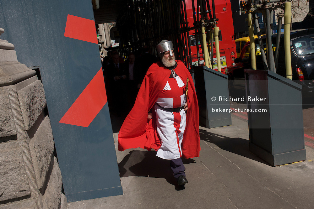 A lunchtime gentleman wearing the red theme of St George, walks through the City of London on St George's Day, when 'Englishmen' celebrate their patron saint.