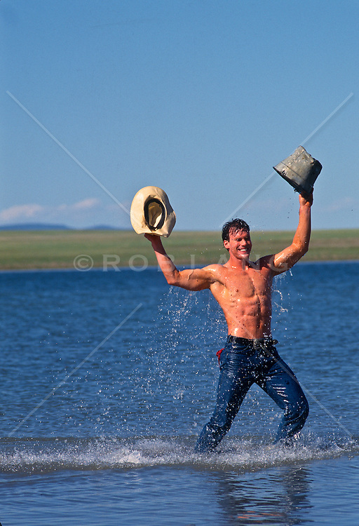 Shirtless man in jeans standing in a lake enjoying pouring water on himself