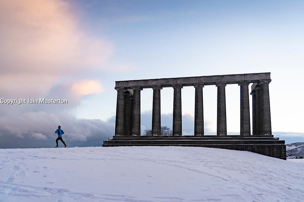 Edinburgh, Scotland, UK. 9 Feb 2021. Big freeze continues in the UK with Storm Darcy bringing several inches of snow to Edinburgh overnight. Pic; Runner on Calton Hill.  Iain Masterton/Alamy Live news