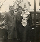 A man and woman posing with there newborn baby